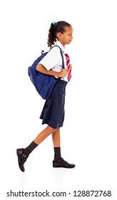 female elementary school student walking on white