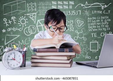 Female elementary school student writing on the book with notebook computer and alarm clock on desk, shot in the class