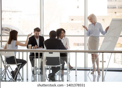 Female employee ask question to middle-aged coach, trainer at company meeting, mature businesswoman discuss strategy, plan with intern, subordinate at briefing, diverse staff at business training