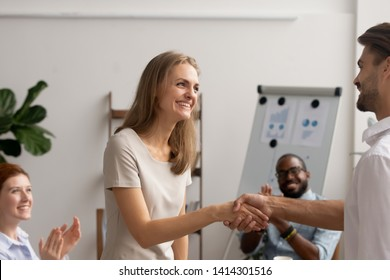 Female employee gets good promotion from executive manager hiring intern handshaking with boss owner. Business team applauding congratulating successful worker with high work results greeting newcomer
