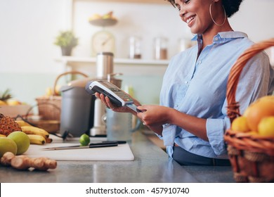 Female employee in a juice bar swiping a credit card in a card reader machine. African woman standing at checkout counter.