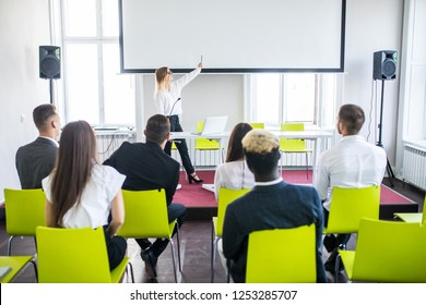 Female employee raise hand asking question to businesswoman making flipchart presentation, woman answering during educational team meeting or corporate training with woman speaker or coach