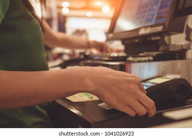 female employee in a store with a credit card in a bank terminal at the cash register in front of a customer