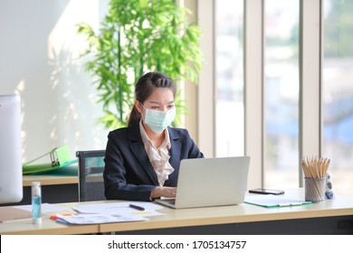 Female employee wearing medical facial mask while working alone because of social distancing policy in the business office reopening during coronavirus or covid-19 outbreak pandemic situation
