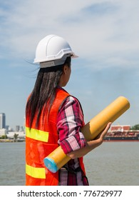 Female engineer is checking work at the shipping dock.