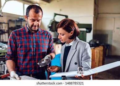 Female engineer consulting with machinist holding cogwheel at industrial manufacturing factory and analyzing blueprint