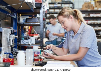 Female Engineer In Factory Measuring Component At Work Bench Using Micrometer
