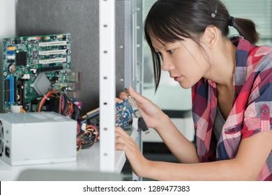 female engineer fixing broken computer hard drive