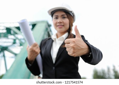 Female engineer holding a blueprint and thumb up,Engineer women smiling portrait picture,Engineer women show hand sinage that's mean Like