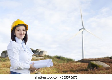 Female engineer holding blueprints at wind turbine site