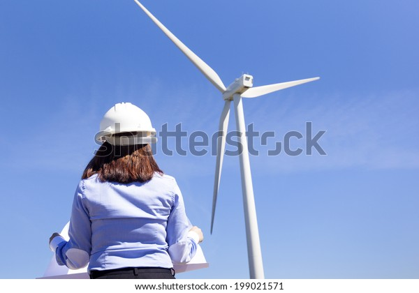 Female engineer holding a blueprints at wind farm