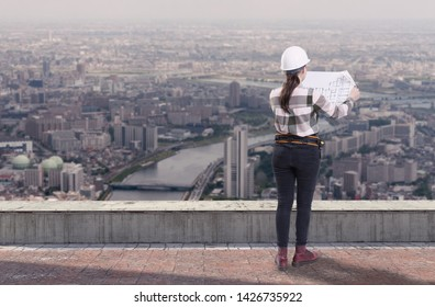 Female engineer holding construction plans standing on the roof top above a city
