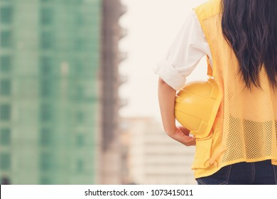 Female engineer holding orange helmet for workers security on  the building being under construction