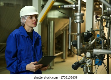 female engineer is holding tablet and conducting an inspection in a production hall at a food factory