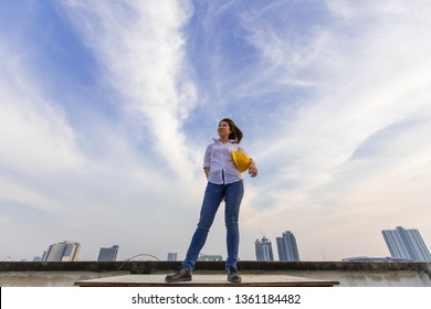 Female engineer holding yellow safty hat standing in high angle with blue sky nature and clouds in background.