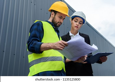 female engineer and male worker in helmets with blueprints on construction