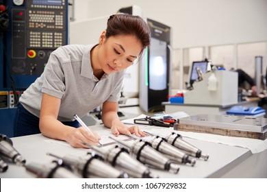 Female Engineer Measuring CAD Drawings In Factory