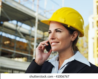 female engineer talking on mobile phone in construction site