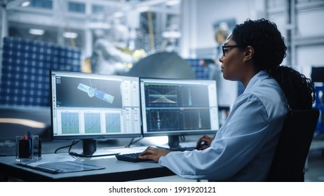 Female Engineer uses Computer to Analyse Satellite, Calculate Orbital Trajectory Tracking. Aerospace Agency International Space Mission: Scientists Working on Spacecraft Construction. Over Shoulder