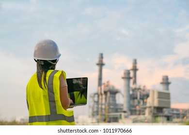 Female engineer is wearing a hard hat on a digital tablet with a power plant on a sunny day.