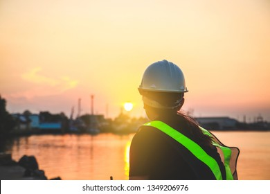 A female engineer wearing a white safety hat, looking at the sun, orange light