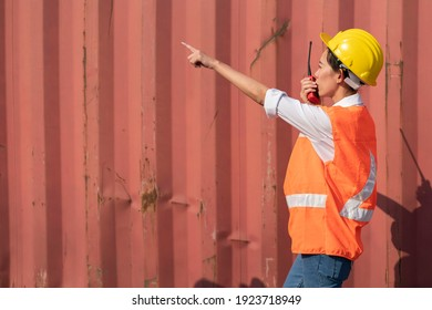 Female engineer wears a uniform, wears a protective helmet, a mobile phone, a walkie-talkie for communication, a corner kiosk sending out goods abroad in a container yard.