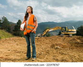 female engineer worker on construction site outdoors with excavator in background