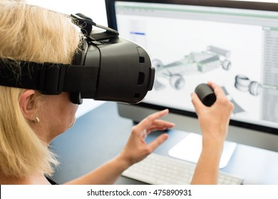 Female engineer working on computer creating a racecar using VR virtual reality glasses and controller. Concept for women in hightech jobs.