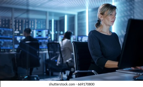 Female IT Engineer Works on Her Desktop Computer in Government Surveillance Agency. In the Background People at Their Workstations with Multiple Screens Showing Graphics.