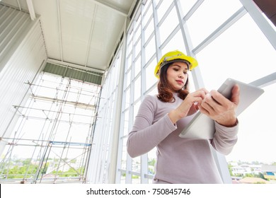 Female engineer in yellow safety helmet is looking to tablet computer while checking for under construction building and curtain wall frame with scaffold in background