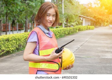 Female engineers hold a communication radio and safety helmet.