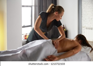 Female enjoying relaxing full body massage made made by masseuse with forearms and cubits in cosmetology spa centre. Body care, skin care, wellness, wellbeing, beauty treatment concept.