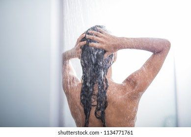 Female enjoying shower while washing hair with shampoo. She gesticulating hands