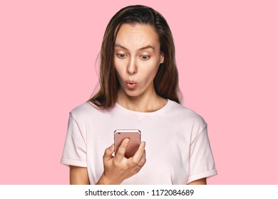 Female enterpreneur or businesswoman being disappointed with news from colleague, reads message on smartphone, shocked to recieve responsibility prepare difficult project for tomorrow`s meeting