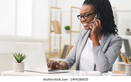 Female Entrepreneur. Cheerful African American Businesswoman Talking On Phone Working On Laptop In Modern Office. Empty Space