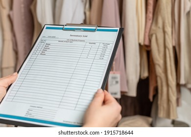 Female entrepreneur holding a clipboard with inventory list while doing inventory in her trendy clothing shop
