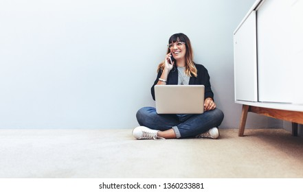 Female entrepreneur managing business sitting at home. Freelancer sitting on floor working on a laptop computer and talking over mobile phone.