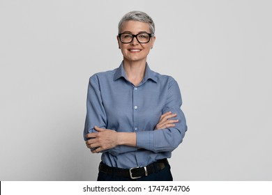 Female Entrepreneurship. Portrait Of Attractive Mature Businesswoman In Eyeglasses Posing With Folded Arms Over Light Background In Studio, Copy Space