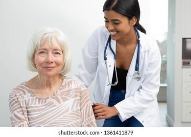 Female ethnic doctor of colour comforting a caucasian elderly senior.
