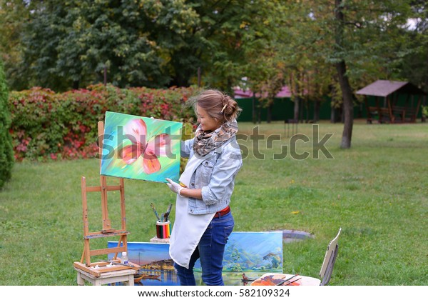 Female European appearance artist evaluates picture and removes from easel, holds and posing with picture which depicts colorful butterfly, smiling and standing in full growth on background of lawn