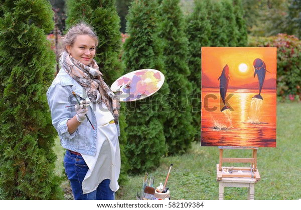 Female European appearance artist evaluates picture and removes from easel,  posing and stands near picture which depicts dolphins on orange cloth, holds brush and palette, smiling and standing in ful