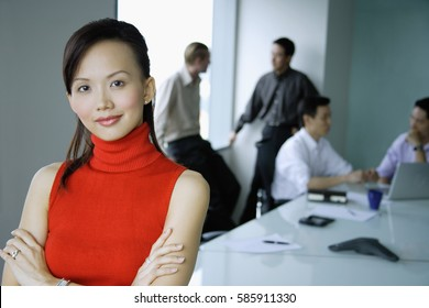 Female executive, arms crossed, looking at camera, people in the background