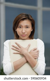 Female executive hugging folders, sad expression
