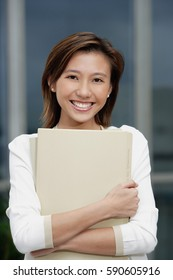 Female executive hugging folders, smiling at camera