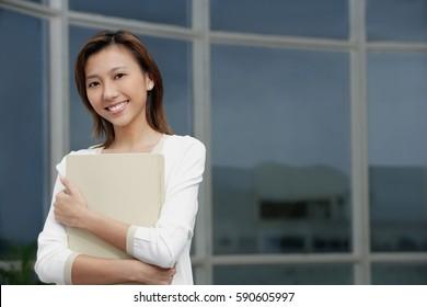 Female executive hugging folders, smiling at camera, portrait