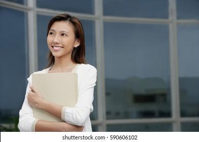 Female executive hugging folders, smiling, looking away