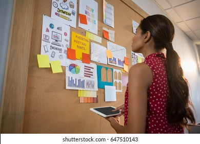 Female executive using digital while looking at the bulletin board in office