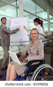 Female executive in wheelchair using laptop computer during presentation