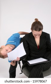 Female executive working on papers while her son looks over her shoulder