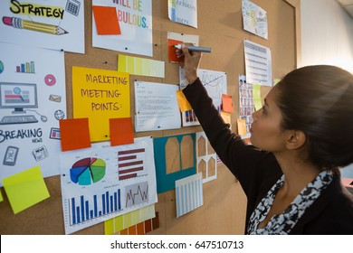 Female executive writing on sticky note at bulletin board in office